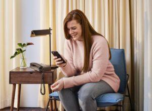 kobieta siedząca ze smartfonem